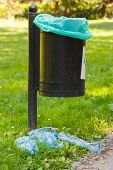 Old trash can in park and heap of plastic bottles concept of environmental protection littering of environmental poster