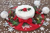 Christmas cake with holly, bauble decorations and winter greenery over oak background. poster