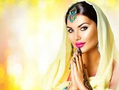 Beauty Indian woman  portrait. Hindu girl hold hands together is symbol prayer and gratitude. Indian model girl with black henna tattoos looking in camera. Mehndi. Indian marriage traditions  poster