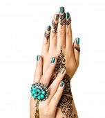 Mehndi tattoo isolated on white. Woman Hands with black henna tattoos. Hands of Indian bride girl with mehndi and perfect emerald manicure and emerald Indian jewels. India national traditions poster