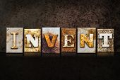 "The word ""INVENT"" written in rusty metal letterpress type on a dark textured grunge background. poster"