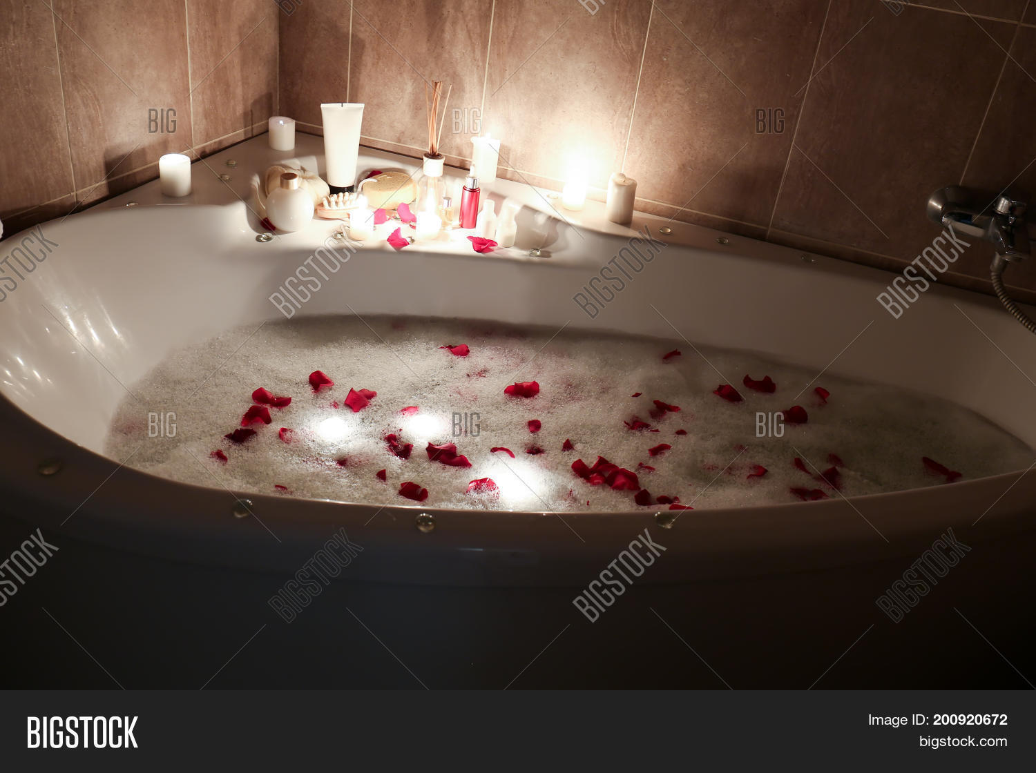 Spa Accessories And Candles On Bathtub Filled With Foam Rose Petals