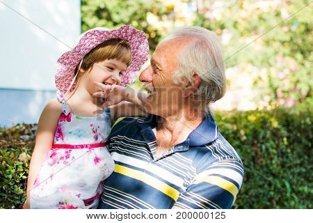 Grandpa And His Granddaughter Laughing Outdoors