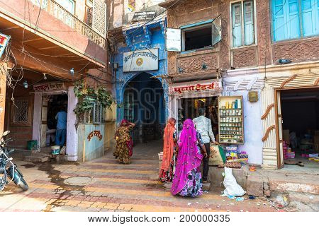 JODHPUR RAJASTHAN INDIA - MARCH 04 2016: Wide angle picture of three women dressing swari indian traditional clothes in Jodhpur the blue city of Rajasthan in India.