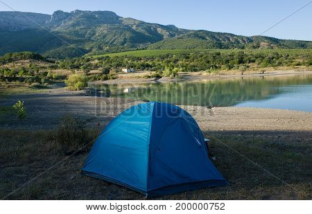 Blue tent on the shore of a mountain lake
