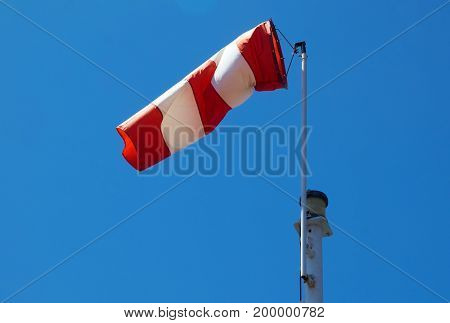Red white striped supplies a wind sock against a blue background