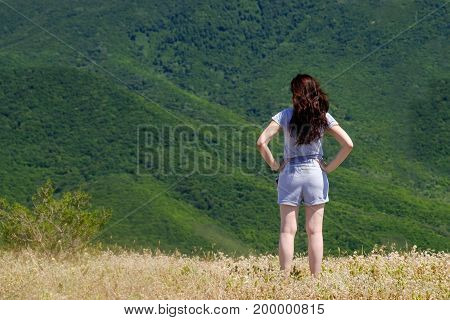 Young girl looking at mountain landscape .