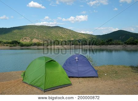 Blue and green tent on the shore of a mountain lake
