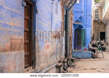 JODHPUR RAJASTHAN INDIA - MARCH 04 2016: Horizontal picture of old indian man sitting in front of the house in Jodhpur the blue city of Rajasthan in India.