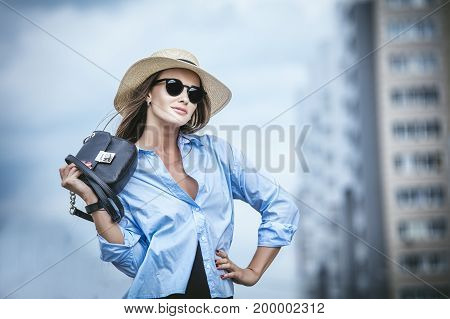 Young beautiful woman model lady fancy shirt and hat with bag on city street