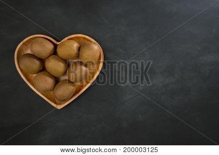 Fresh Kiwi Fruit In Heart Shaped Wooden Plate