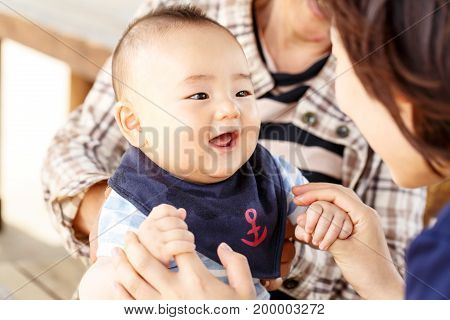 Happy together - smiling baby with his mother and his grandmother outdoor