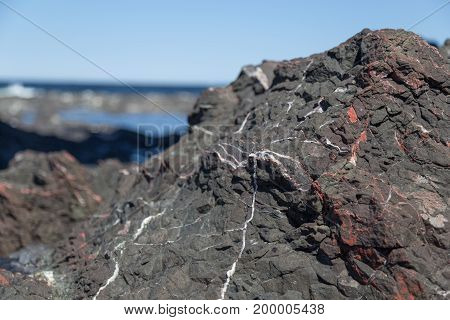 Black Rock With White And Red Veins
