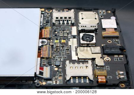 Photo image. Close up of smart phone internal hardware. Repair process illustration