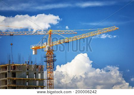 The crane elevating on the blue sky backgroung