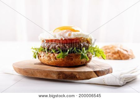 Close-up of beef burger on white background. Hamburger - bun grilled meat burger lettuce tomato and fried egg.