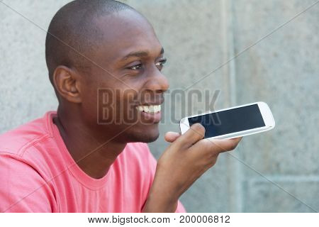 Hairless african american man speaking voice message outdoor in the summer