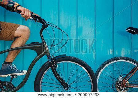 Unrecognizable Young Man Sitting With A Bicycle Along A Blue Wall Background Daily Lifestyle Urban Resting Concept