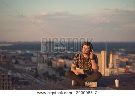 A hipster guy listens to music on headphones on the roof of a high-rise building. He closed his eyes and enjoyed the moment. Freelancer in search of inspiration.