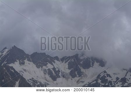 Snow-covered mountain range hiding behind the clouds view from the of Elbrus Kabardino-Balkaria Russia