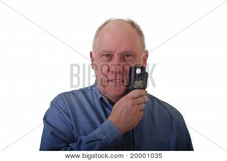 Older Man In Blue Denim Shirt Holding Light Meter To Face