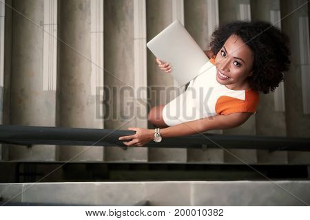 Pretty young business lady standing on the stairs with laptop, view from above