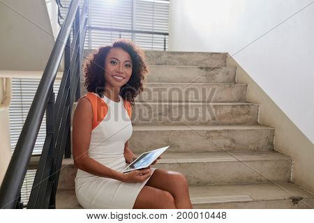 Pretty female business executive sitting on the stairs with digital tablet in hands