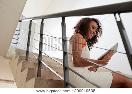 Smiling Vietnamese woman sitting on stairs and reading news on digital tablet