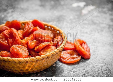 Dried Apricots In Basket. On Rustic Background .