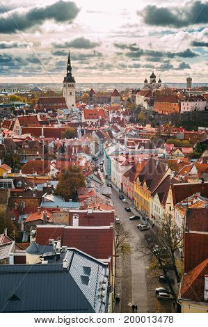 Tallinn city from above view against sun and cloudscape. Sunlit old town vertical view by autumn day
