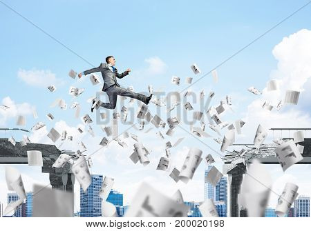 Businessman jumping over gap with flying paper documents in concrete bridge as symbol of overcoming challenges. Cloudly skyscape on background. 3D rendering.