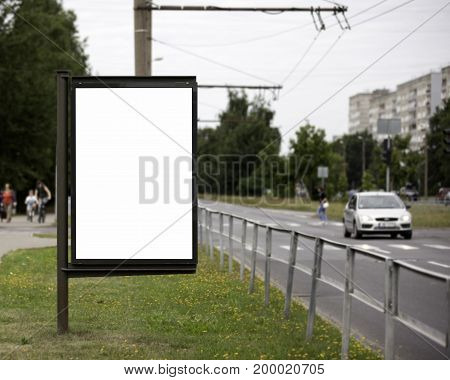 Blank Billboard on City Street. Transport and people in the background.