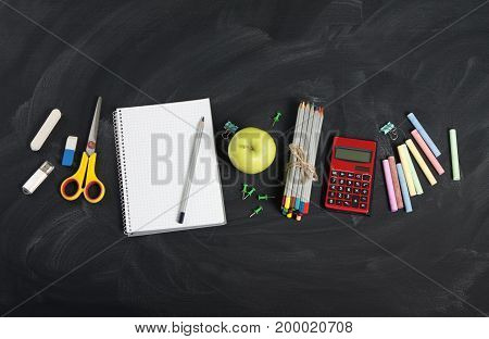 School and office supplies on classroom blackboard. View with copy space