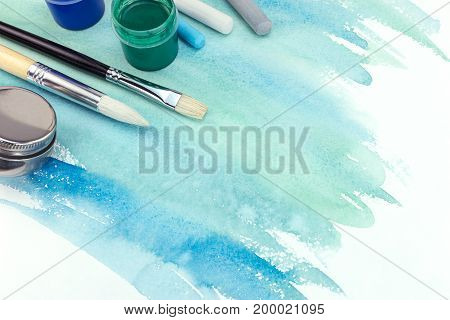 Paintbrushes, Paints And Pastel Chalks On Green Blue Watercolor Background