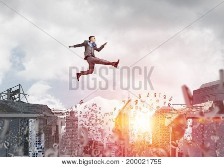 Businessman jumping over gap with flying letters in concrete bridge as symbol of overcoming challenges. Cityscape and sunlight on background. 3D rendering.
