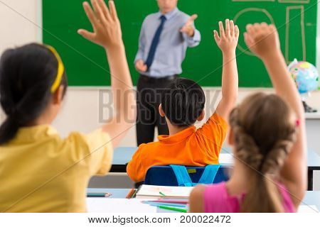 All the pupils rising hands as they want to answer, rear view