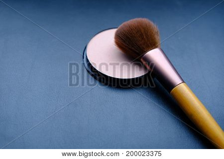 Beige face powder and brush for make up isolated on blue background.