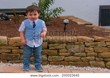 Little boy in suit with vest and tie stands in front of a wall of sand stones.