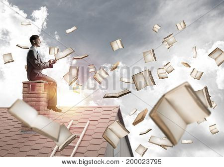 Young businessman sitting on house roof with smartphone in hands