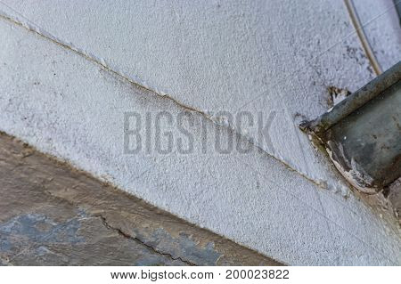 Small cracks in the plaster on the outer wall of the caused by a structural damage.