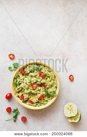 Bowl of guacamole dip  with ingredients. Rustic background, top view, lots of copy space