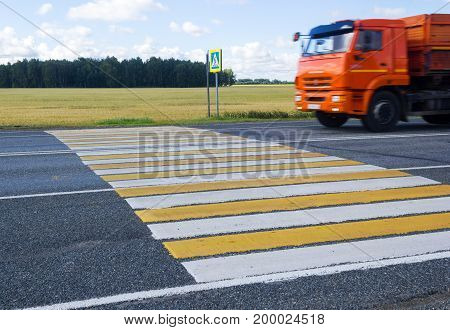The truck goes through a pedestrian crossing on a country road