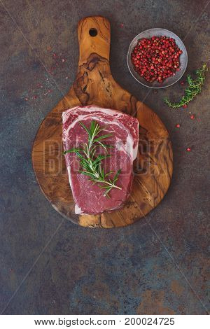 Raw beef steak on a cutting board with rosemary and spices,  top view, lots of copy space