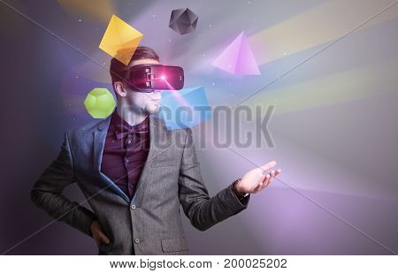 Amazed businessman with virtual reality colorful geometric shapes in front of him
