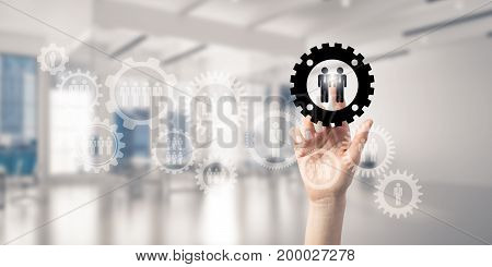Close of woman hand touching gears on screen with finger and office at background