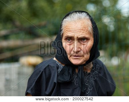 Old woman in black crape kerchief outdoor with a sad expression