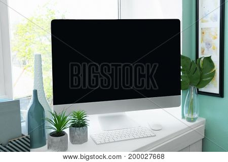 Modern comfortable workplace with computer on window sill at home