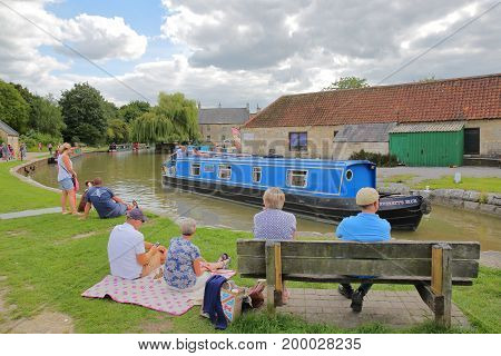 Bradford on Avon, UK - AUGUST 13, 2017: People enjoying a summer day at Canal Wharf with colorful barges on Kennet and Avon Canal
