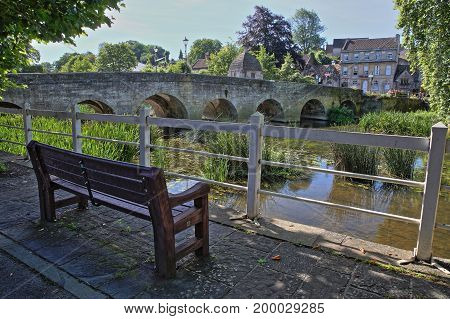 The Old Town Bridge over the river Avon with a wooden bench in the foreground, Bradford on Avon, UK