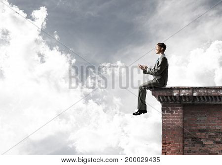 Young businessman sitting on building top with cell phone in hands